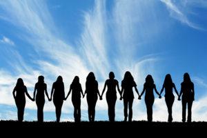 Mehrere Menschen stehen sich an den Händen haltend und sehen gemeinsam in die Ferne.