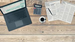 Holzschreibtisch mit Laptop und Taschenrechnung sowie Kaffee, Zeitung und Stift