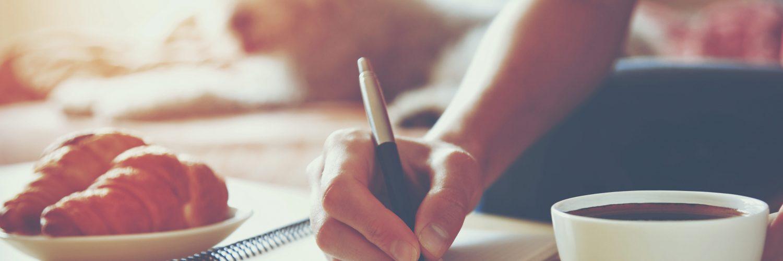 Frauenhänden mit Stift schreiben auf Notebook mit Kaffee am Morgen